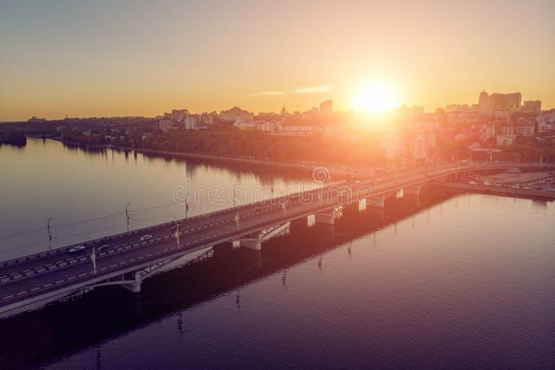 Chernavsky桥梁鸟瞰图在河的有反射、汽车通行和沃罗涅日市的有大厦的在日落背景 免版税库存图片