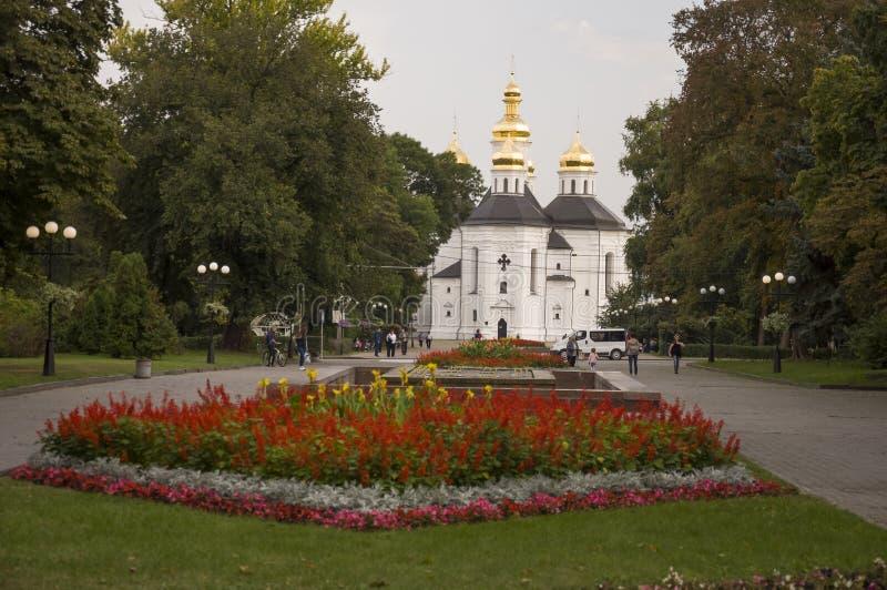 Chernigov, de Oekraïne 15 september, 2017 Christelijke orthodoxe witte kerk met grijze koepels en gouden kruisen Park met Bloemen stock foto's