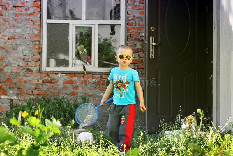 Chernihiv, de Oekraïne - Mei 19, 2019: Een kleine jongen speelt badminton op de straat stock afbeeldingen