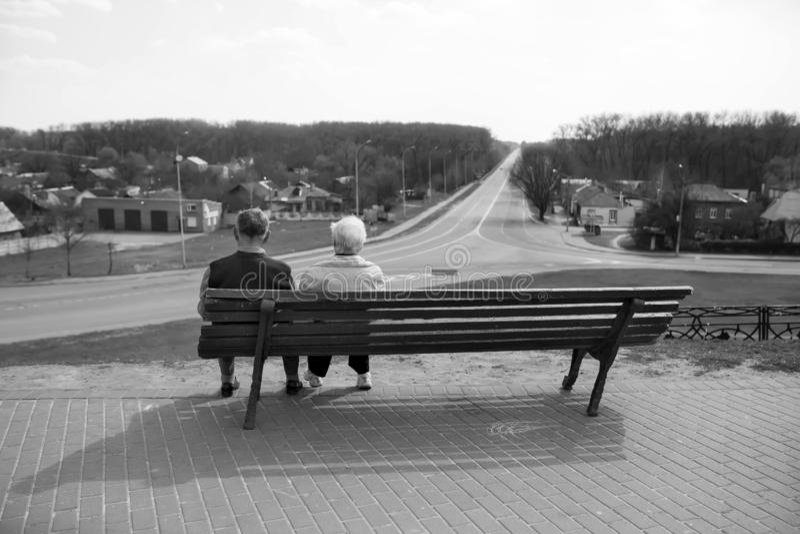 Chernihiv ucrania 12 04 2015 más viejas personas se sientan en un banco y una mirada en la distancia La foto está en blanco y neg foto de archivo