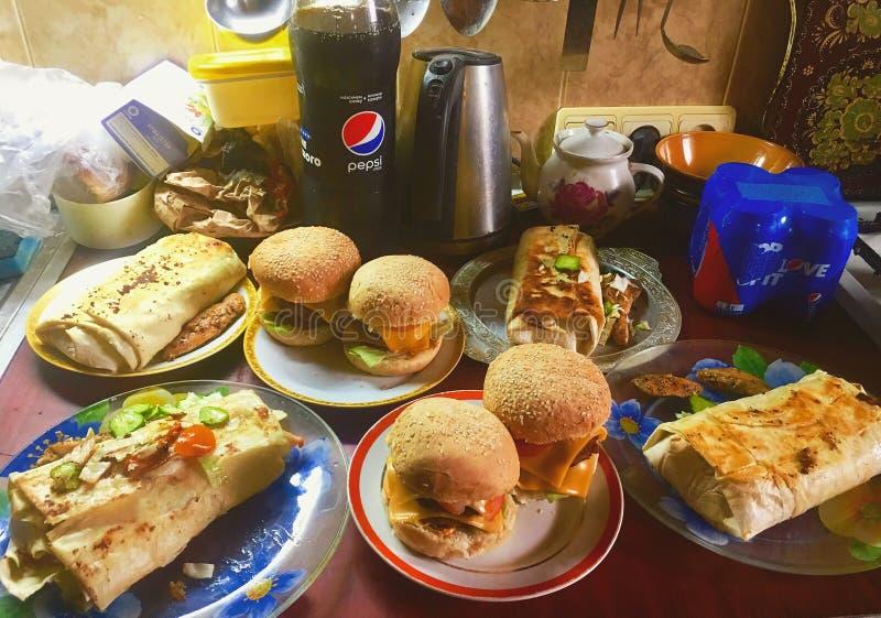 Chernihiv Ukraina, Sierpień, - 3, 2019: Jedzenie na stole Hamburgery i Shawarma z koka-kola obraz royalty free