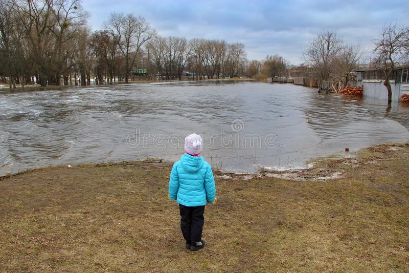 Child watching river flooding in city after melting snow in spring. Natural disaster. Chernihiv / Ukraine 02 April 2018: Child watching river flooding in city stock image
