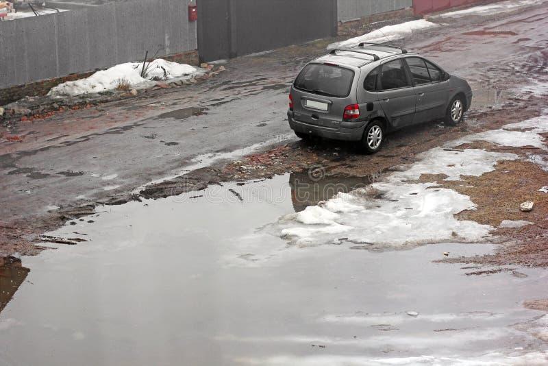 Chernivtsi, de Oekraïne - Maart 31, 2018: Regenachtige dag De privé auto Renault bevindt zich dichtbij een groot gat stock foto