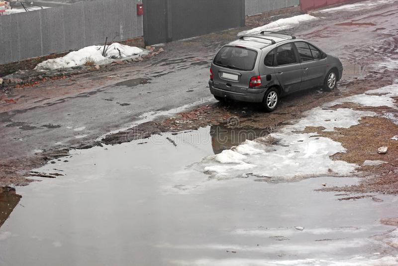 Chernivtsi, Ucrânia - 31 de março de 2018: Dia chuvoso O carro privado Renault está perto de um furo grande foto de stock