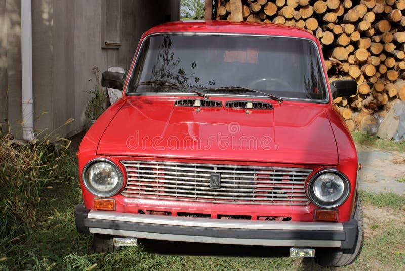 Chernivtsi, Ucrânia - 13 de setembro de 2018: VAZ idoso 2101 do carro do russo Carro velho vermelho em um fundo da lenha foto de stock
