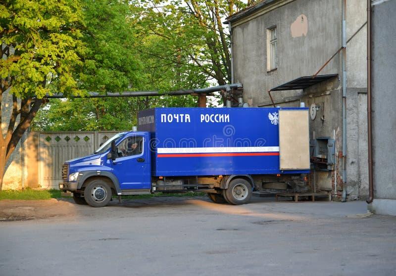 CHERNYAKHOVSK RYSSLAND De ryska stolpelastbilkostnaderna på att lasta av av brevskickande i stolpen - kontor arkivfoto