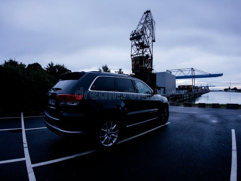 Cherokee виллиса грандиозное припаркованное на промышленном заходе солнца района доков порта стоковая фотография rf