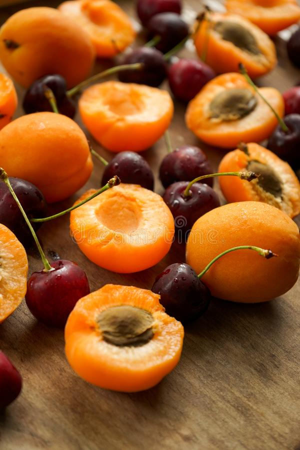 Cherries and apricot halves with seeds. Selective focus,bright, Mature apricots, seeds and berries ripe cherry on a wooden Board textured with drips royalty free stock photo