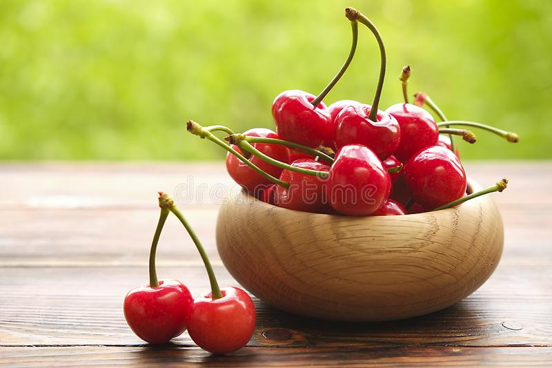 Cherries in a bowl on wooden surface, spring / summer, green tree leaves background. stock image