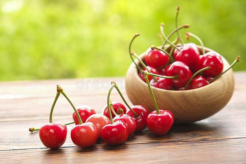 Cherries in a bowl on wooden surface, spring / summer, green tree leaves background. stock photo