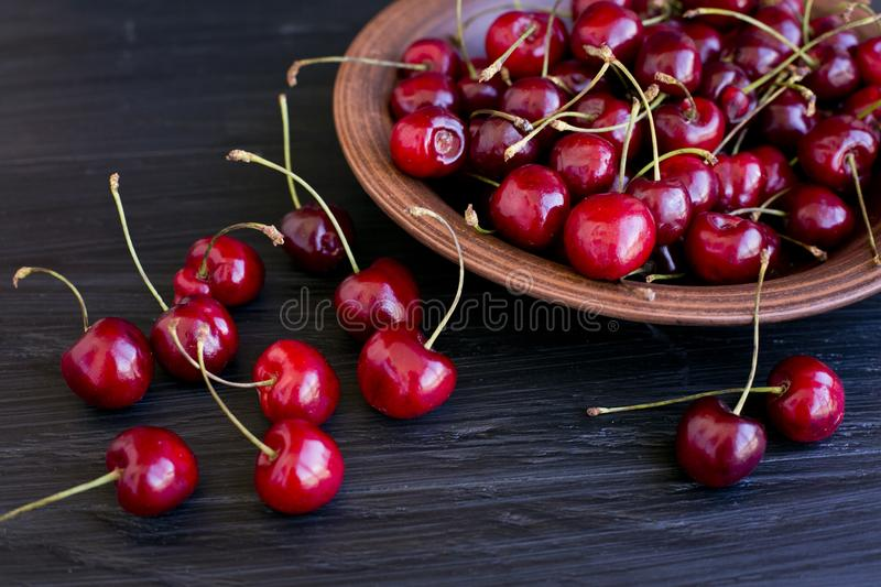 Cherries on a clay plate. Still life on a black background. Red cherries. Fruit plate. Summer mood. Delicious snack stock image