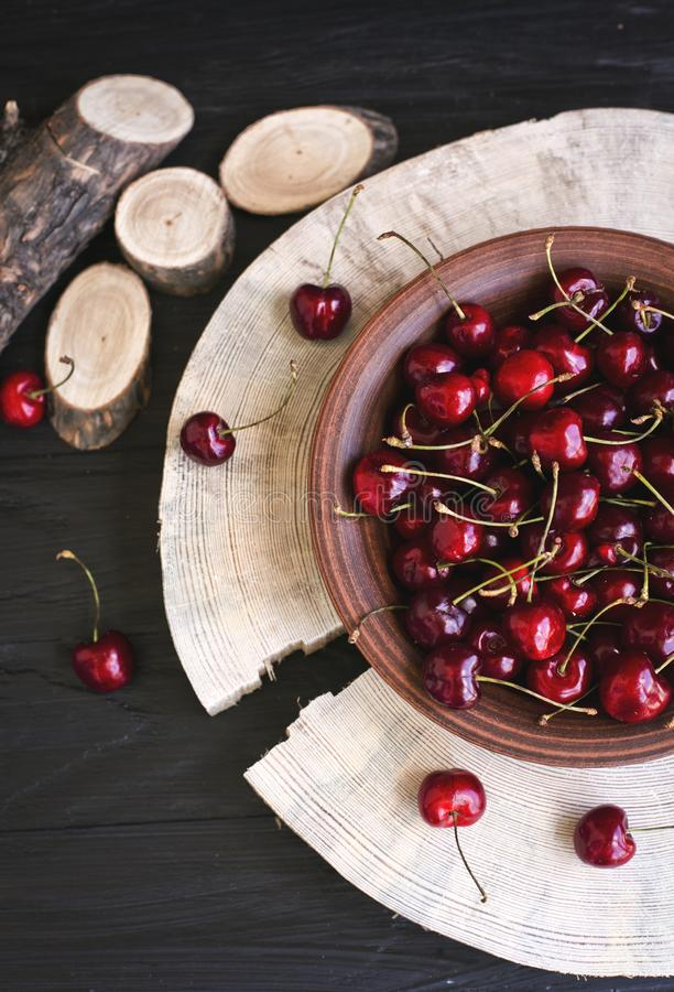 Cherries on a clay plate. Still life on a black background. The spinals of the tree lie side by side. The plate stands on a large piece of wood. Red cherries stock images