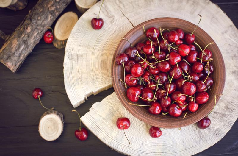 Cherries on a clay plate. Still life on a black background. The spinals of the tree lie side by side. The plate stands on a large piece of wood. Red cherries stock photography