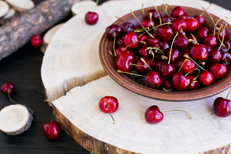 Cherries on a clay plate. Still life on a black background. The spinals of the tree lie side by side. The plate stands on a large piece of wood. Red cherries stock image