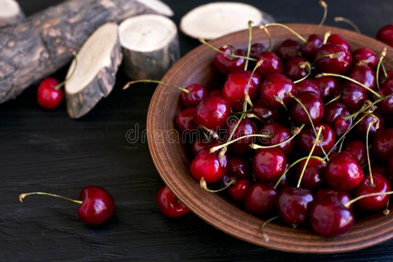 Cherries on a clay plate. Still life on a black background. The spinals of the tree lie side by side. Red cherries. Fruit plate. Summer mood. Delicious snack royalty free stock photos