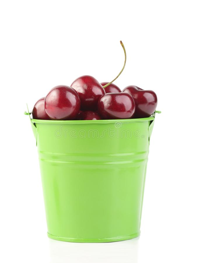 Cherries in green pail isolated on white. Background stock image