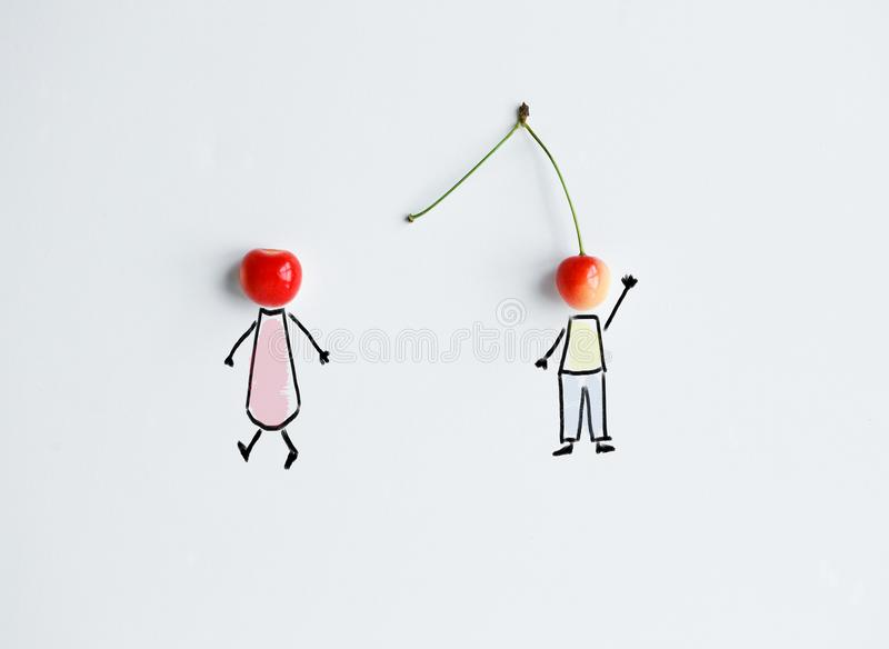 Cherries with hand drawing shapes of loving couple royalty free stock images