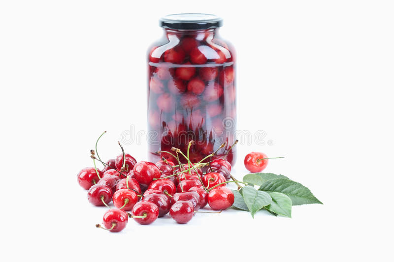 Cherries beside jar of cherry compote royalty free stock photo