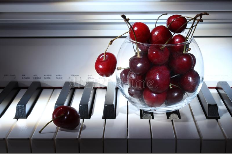 Cherries vase on piano keys. Abstract wallpaper. Music concept. Picture of wallpaper stock photo