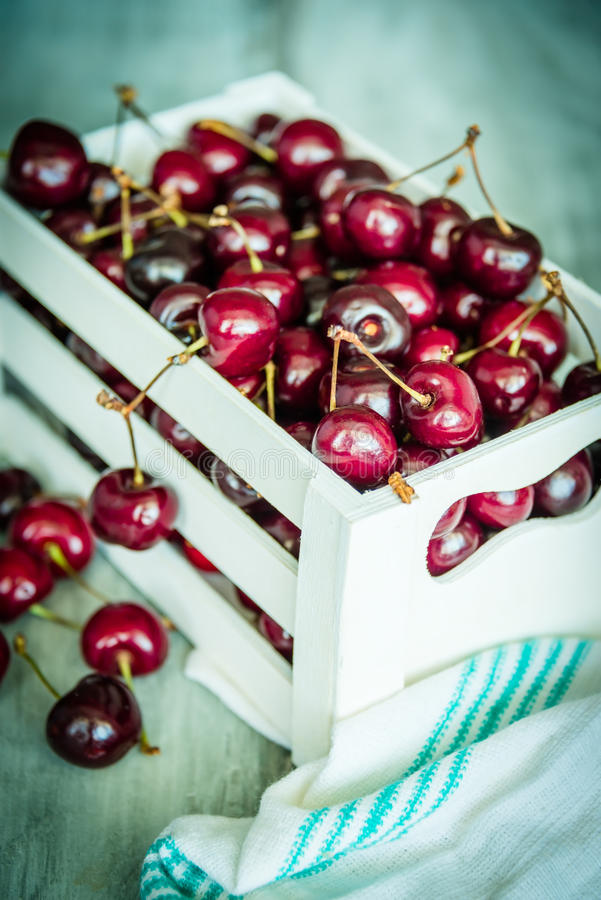 Cherries in a white wood crate over a wood background stock image