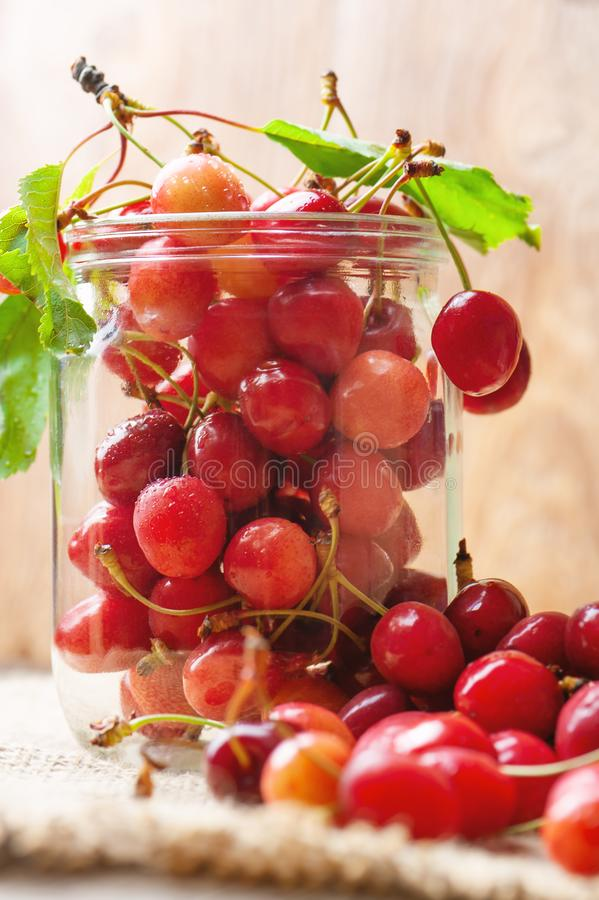 Cherries on wooden table in glass jar.  stock photo