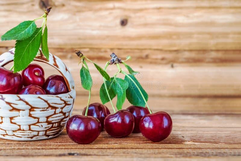 cherry świeże Dekoracyjny kosz z czereśniowymi jagodami na drewnianym tle fotografia stock