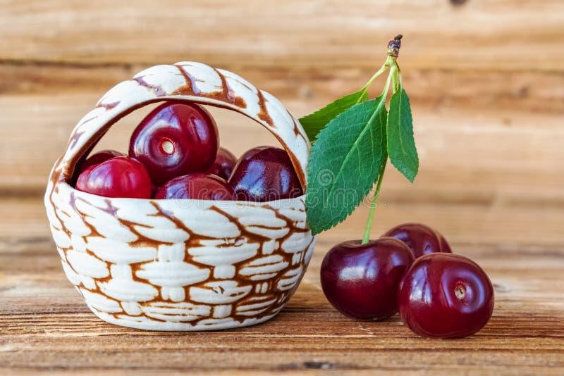 cherry świeże Dekoracyjny kosz z czereśniowymi jagodami na drewnianym tle zdjęcia royalty free