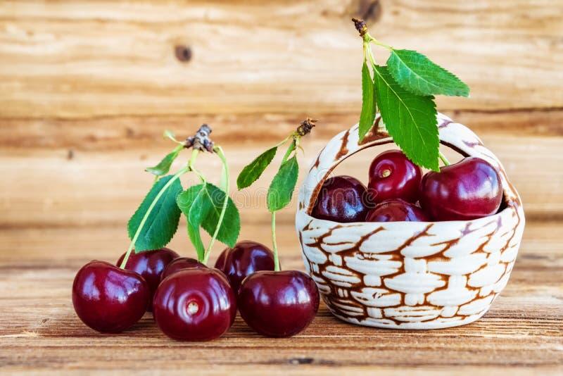 cherry świeże Dekoracyjny kosz z czereśniowymi jagodami na drewnianym tle obraz stock