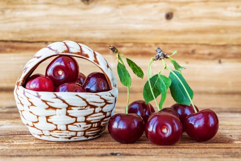 cherry świeże Dekoracyjny kosz z czereśniowymi jagodami na drewnianym tle obrazy stock