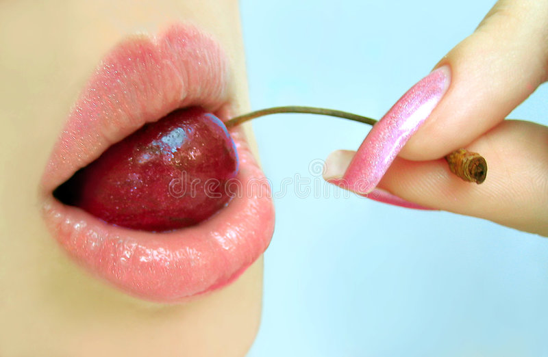 Cherry. Rose lips with cherry in teeth stock images