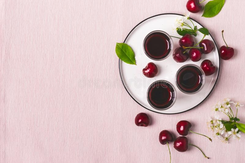 Cherry alcohol drink liquor or brandy on pink background stock photography