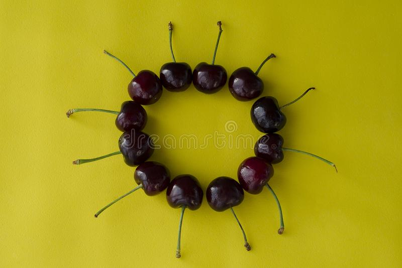 Cherry berries on a bright yellow background in the form of a circle royalty free stock photos