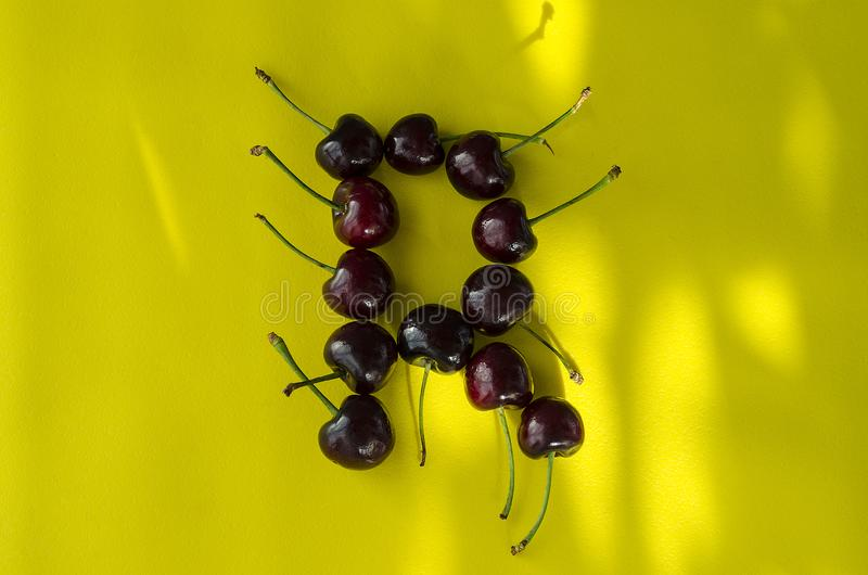 Cherry berries on a bright yellow background in the form of the letter R with sun highlights royalty free stock photography