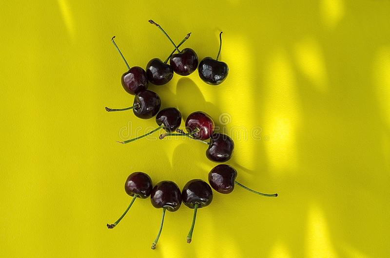 Cherry berries on a bright yellow background in the form of the letter S with sun highlights royalty free stock images