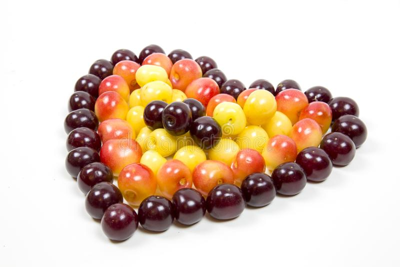 Cherry berries cherries in the form of a heart of red pink yellow isolated on a white background, a place for the text of the conc stock image