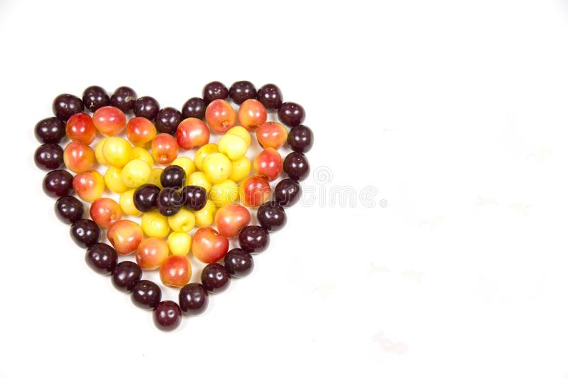 Cherry berries cherries in the form of a heart of red pink yellow isolated on a white background, a place for the text of the conc royalty free stock photo