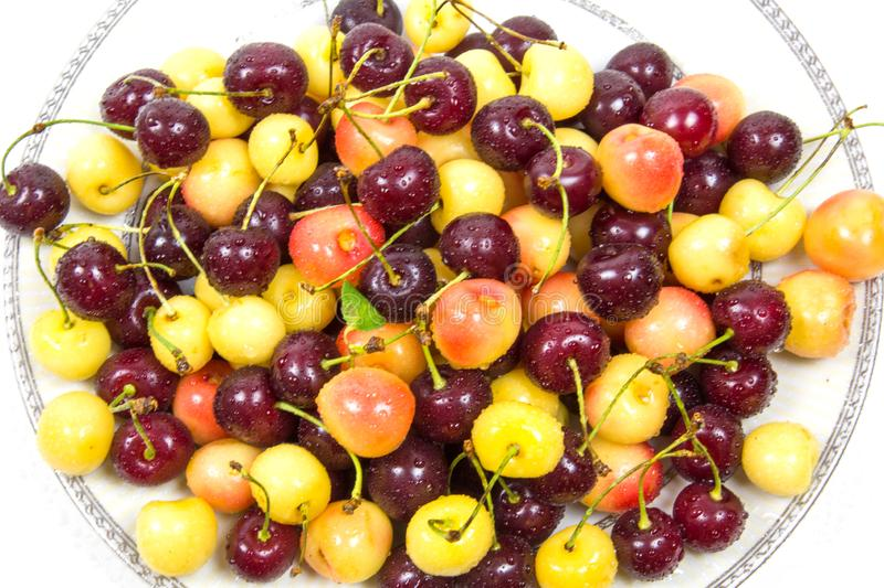 Cherry berries cherries red pink yellow with cuttings leaves with water droplets on a plate. stock photos