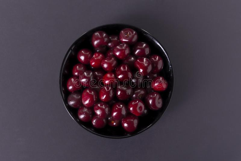 Cherry in a black plate on a dark background stock photography