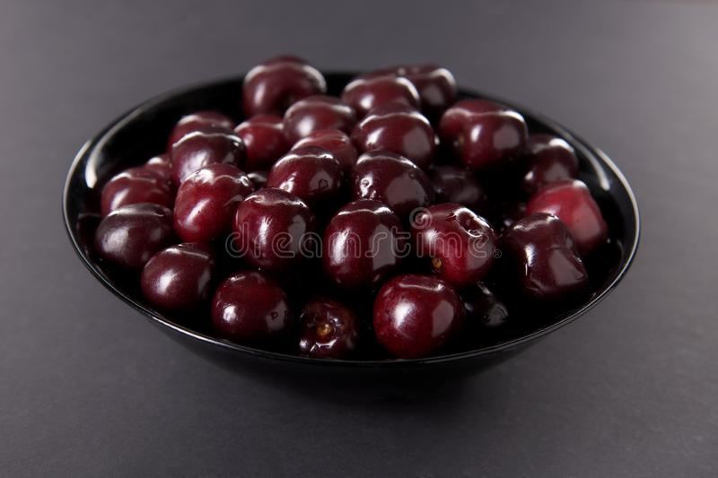 Cherry in a black plate on a dark background stock image