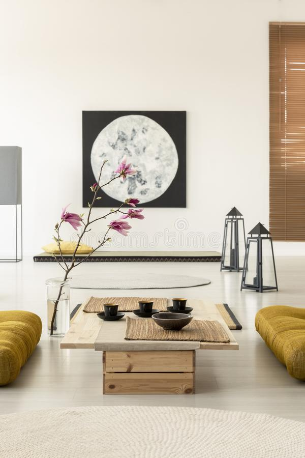 Cherry blossom in a Japanese living room interior with a painting, coffee table with cups and yellow pillows on the floor stock images
