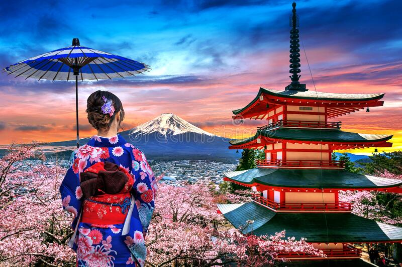 Cherry blossoms in spring, Asian woman wearing japanese traditional kimono at Chureito pagoda and Fuji mountain at sunset in Japan stock photos