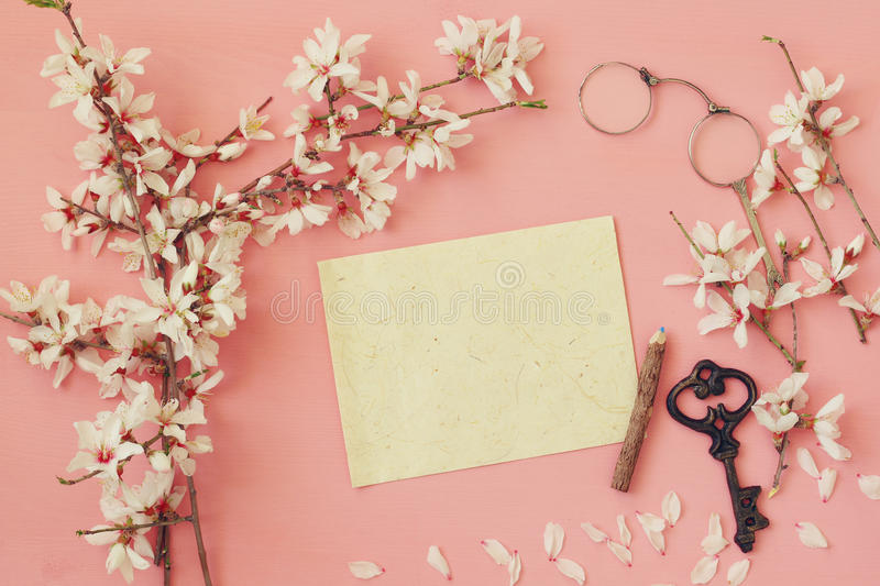 Cherry blossoms tree and blank paper for letter. Top view image of spring white cherry blossoms tree and blank paper for letter on wooden background stock image