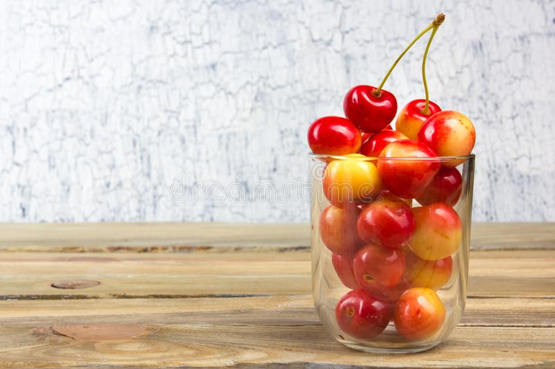 Cherry in a bowl. Fresh yellow cherry. Cherry on a white wooden background. The concept of a healthy diet. Berries royalty free stock photo