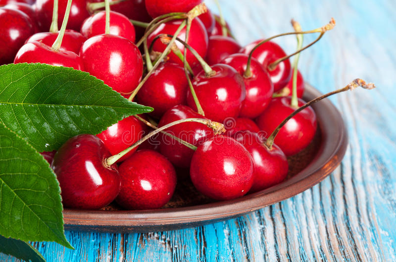 Cherry in a clay dish. Red sweet cherry and green leaves in a clay dish on a blue wooden background royalty free stock photo