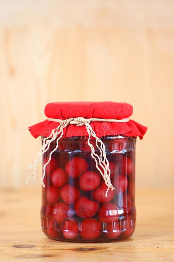 Cherry compote. In glass jar, studio shot royalty free stock images