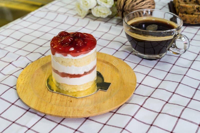 Cherry Cream Cake på träplatta- och kaffekoppen royaltyfri bild