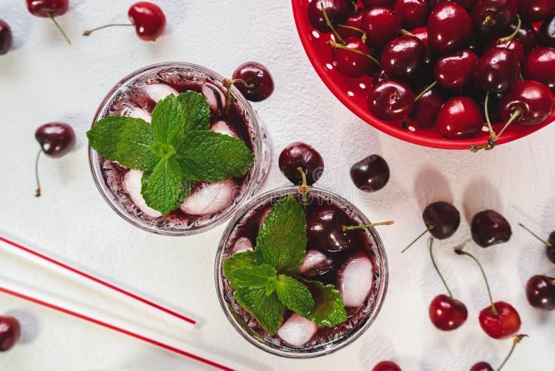 Cherry Drink con los cubos de la menta y de hielo, y cerezas frescas en el fondo blanco fotografía de archivo libre de regalías