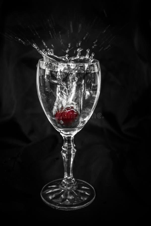Cherry Dropping im Weinglas stockfotografie