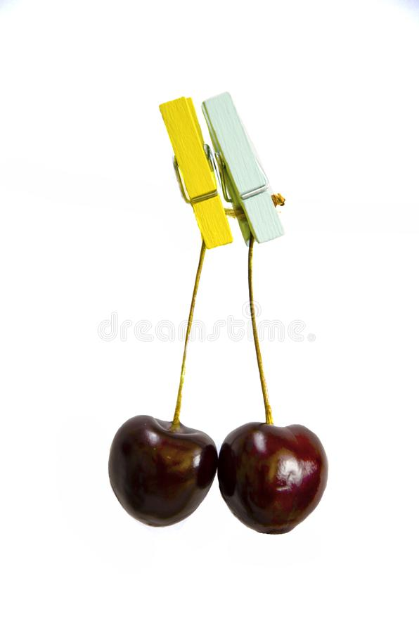 Cherry hanging on a clothespin on a rope stock image