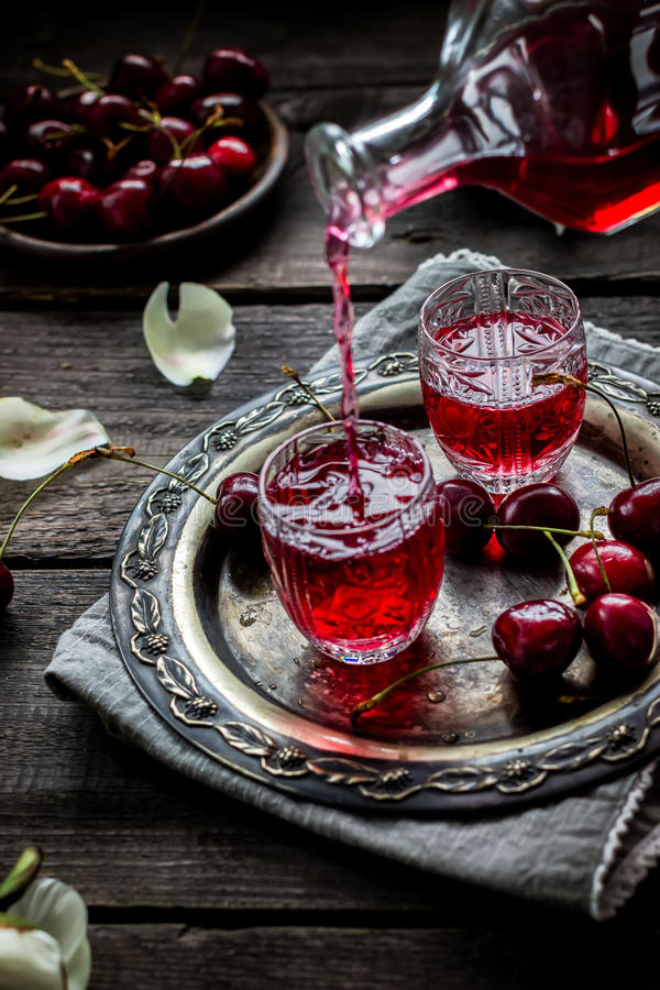 Cherry homemade liquor flowing in a vintage glass. stock photography